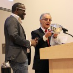 Alain Mabanckou receiving the 2016 Puterbaugh Pewter Bowl from World Literature Today executive director R.C. Davis