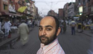 Writer Mohsin Hamid pauses in the middle of a street to look at the camera